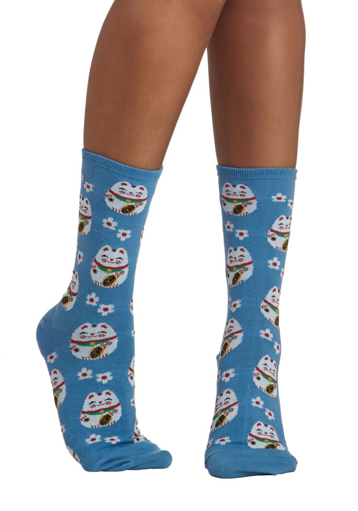 Wear these blue knit socks as your lucky charm! A red-and-white floral print featuring the iconic lucky cat will surely provide all of the good vibes you may ever need. These mid-calf-length socks are perfect for completing a playful look!