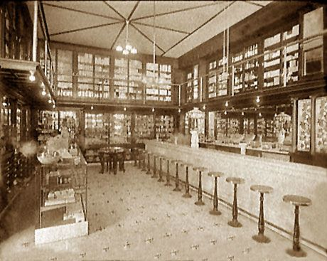 The above photo shows a typical pharmacy soda fountain, about 1900. Notice the ornate Tiffany-style lighting fixture centered on the marble countertop and the stained glass decorating the sides of the mirror-backed rear cabinet. The customers enjoyed sipping their fizzy sodas while seated comfortably on the round wooden stools.