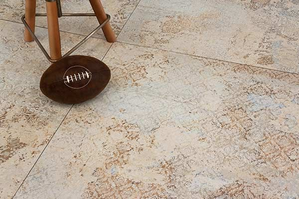 closeup of a living area floor with Apirici Carpet series in Vestige Natural porcelain tile install, a design created with inspiration from an 18th century antique carpet