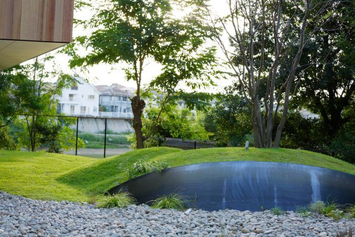 rectangular-house-opens-wide-towards-lake-surface-surrounded-rich-greenery-25