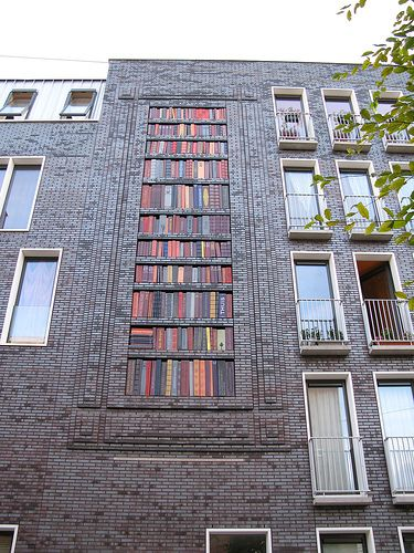 """Library Facade by Liesbeth den Toom via newyorker: The building is situated in a part of Amsterdam's Oud-West neighbourhood where many of the streets are named for Dutch authors and poets from the 18th and 19th century. The library, which measures 2.5 x 7.5 m and was unveiled in November 2006, consists of ceramic """"books"""" with titles taken from poems by those authors. #Architecture #Amsterdam Liesbeth_den_Toom #newyorker"""