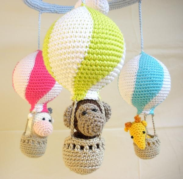 This hot air balloon mobile has a fun, colorful design to keep your baby entertained. This baby mobile features three hot air balloons with bright and attractive colors, and three plush animal toys ( a yellow giraffe, a white and pink cow, and a brown monkey ) which will keep your baby interested with their detailed designs and friendly faces. This item is totally handmade using 100% cotton yarn. The hot air balloons measure 20 cm (7,8 inches) height, and 27 cm (10,6 inches) circumference…