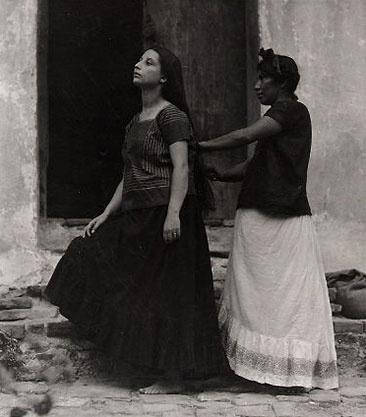 """Manuel Alvarez Bravo era un fotografo desde 1902-2002. Sus fotos ilustraron la gente real en mexico y tambien su cultura folclórico, en la que la mayoría de sus fotos tienen el propósito de capturar la belleza y el estado natural de México. Esta foto se puede representar la obra de """"Bernarda Alba"""" porque en la foto, la chica cepillado el pelo de la otra chica indica que uno esta cuidando al otro. Esto compara con Poncia en la obra porque ella encarga a las chicas en la casa."""