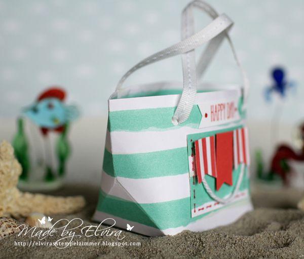 """Eine Strandtasche mit dem Gift Bag Punch Board Normalerweise wird das gefaltete Dreieck nach innen gebogen, ich habe es aber nach außen gedrückt, und auch auf die Seitenfalzlinien verzichtet. Für die Fähnchen habe ich Farbkarton in einer der neuen In Colors - Melonensorbet verwendet. Die gestreiften Fähnchen sind aus einem neuen """"Umschlagpapier"""" - auch in den neuen In Colors, und ergänzen so den maritimen Style."""