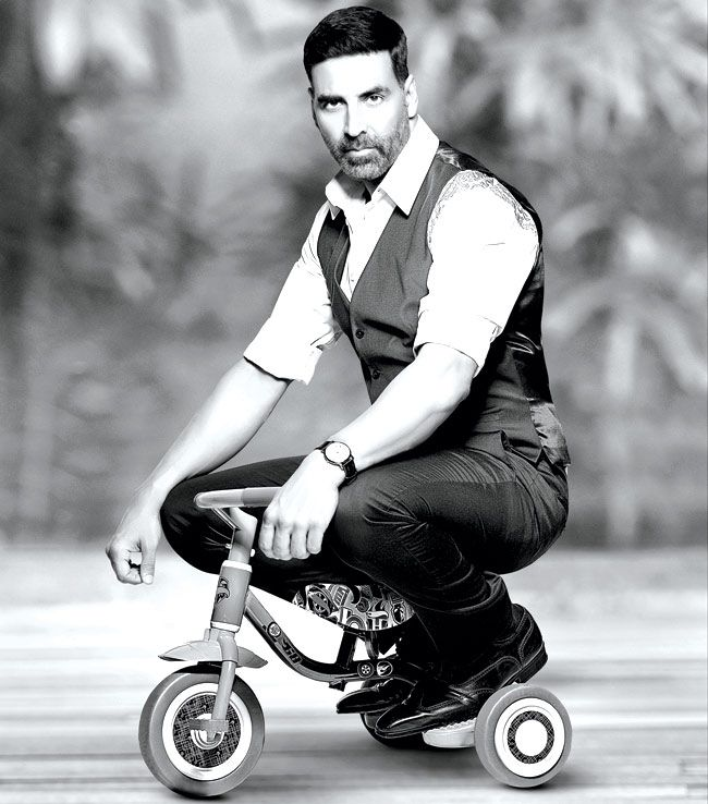 Akshay Kumar on a kiddie tricycle looks cute, charming and cool, all rolled into one frame in Daboo Ratnani's 2015 calendar. #Bollywood #Fashion #Style #Handsome