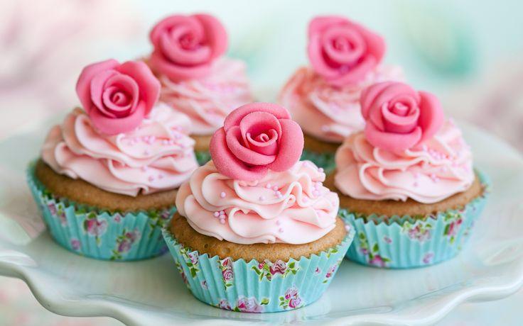 een mooie cup cake met rozen er op