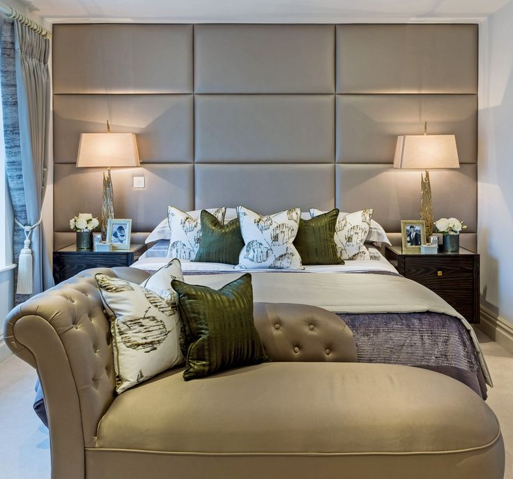 The luxurious bedroom in our exclusive Berkeley Group waterfront home - with lavish padded panelled headboard and wall in a soft gold leather effect Kirkby Design fabric, flanked by beautiful Julian Chichester bedside tables.
