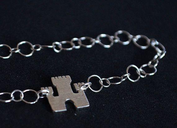 Questo versatile bracciale è formato da una catena in argento 925 e un castello, realizzato a mano. Mi sono ispirata alla serie trono di spade che adoro.  Bracciale perfetto da indossare solo o insieme ad altri bracciali. Ideali per se stessi o come regalo per una persona cara.  --- Dettagli --- Materiale: argento 925. Finitura: graffiata/ lucida Dimensione castello: 1,1x 1,3 cm circa (0,43x0,51) Chiusura: Moschettone  *** COME ORDINARE *** 1. Nel primo menù a tendina, seleziona la lungh...