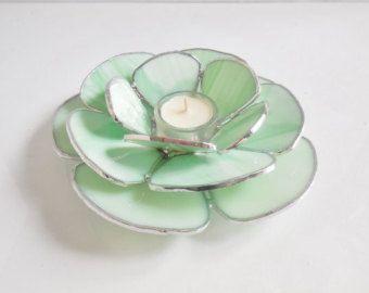 Sostenedor de vela 3D único con una flor. Votiva. Uno de los tipos. Cosa bonita para la decoración de su hogar. Puede ser utilizado como un sostenedor de vela - votivo y también como un anillo en el lugar de descanso.   Arte en vidrio: azul claro, rosado, pálido, blanco, rosado. 4 abalorios de cristal color de rosa para un acento. Un cucurucho pequeño para tus anillos ha añadido en el medio. (El anillo que puedes ver en el cuadro no se incluye).  Medidas: 9 1/4 de x 7 3 flores 2.5 H  Se ...