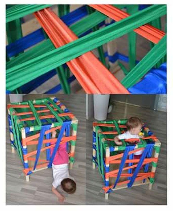 Cubo hecho con listones de madera y las paredes son cintas de tela (un poco elásticas para evitar roces en la piel del pequeñ@) para que el niñ@ pueda entrar y salir sorteando las cintas. Estos movimientos permiten trabajar y desarrollar la motricidad gruesa. Un reto que a los niños les encanta.