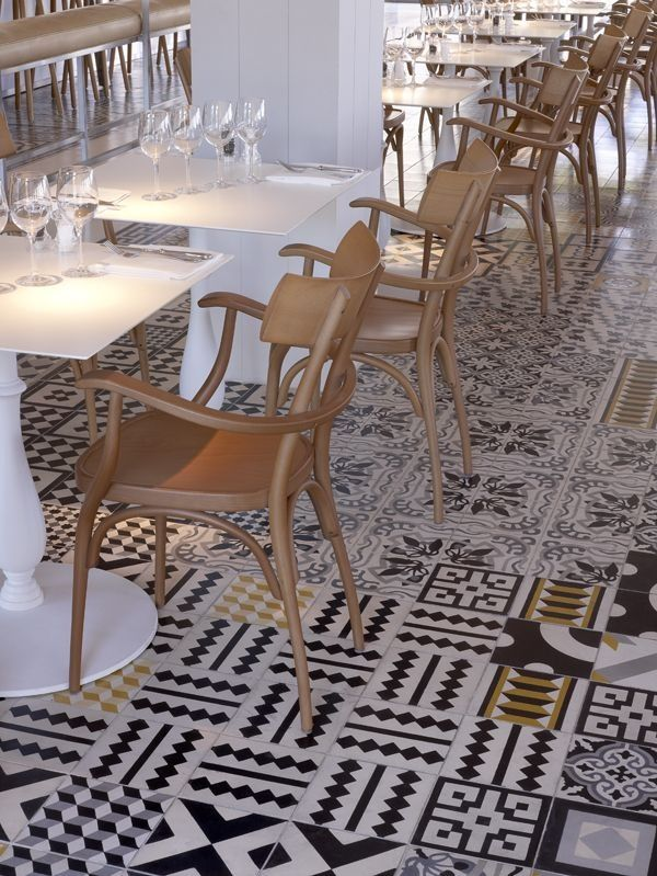 bar/restaurant black and white graphic tile floor and gold wood chairs