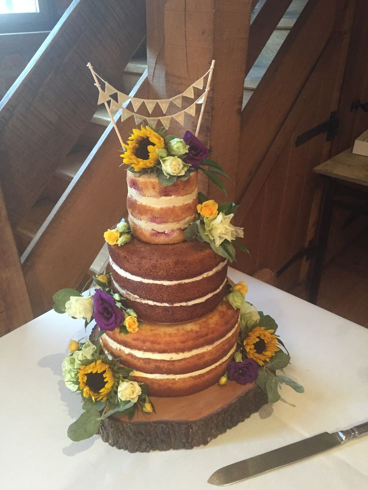A naked wedding cake decorated with sunflowers on a log slice cake stand and bunting for a rustic barn wedding. Sunflowers and roses, purple and yellow, naked cake.