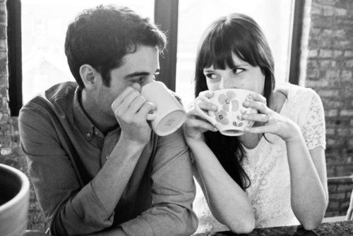 Cute pose for coffee loving couples. Natural moments, shared activity, mugs hide the face, but the eyes connect the two affectionately