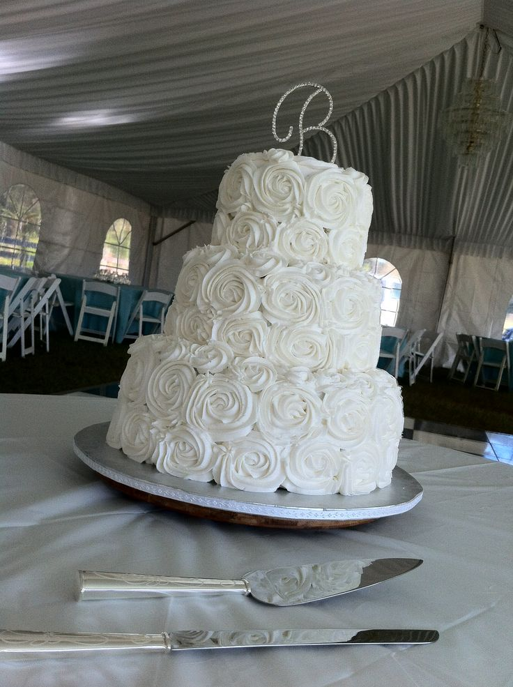 Buttercream roses cake - maybe roses on the top and bottom tiers with a plain white middle tier? Or maybe a sparkly middle white tier (looks like they put granulated sugar on the outside)