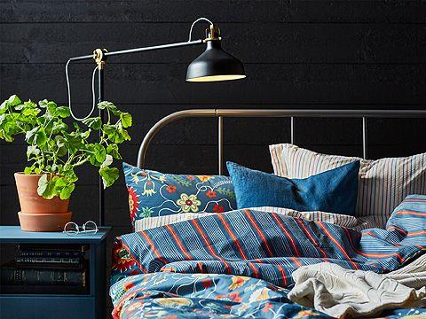Struttura letto in metallo nero con biancheria in blu, rosso, giallo e bianco. Lampada da terra nera – IKEA