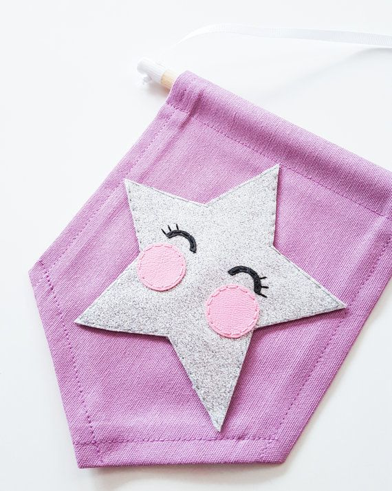 This is a lovely mini wall banner which would look lovely in your childs nursery or playroom ♥  This banner is made from a lilac heavy canvas material - which has been machine stitched for stability on all sides, the star is made from a super shiny silver glitter fabric, and the cheeks and eyes are made from a super soft leatherette fabric - all individually hand stitched to perfection!  **This banner can be made in a choice of 22 different colours, please look at the colour options in…