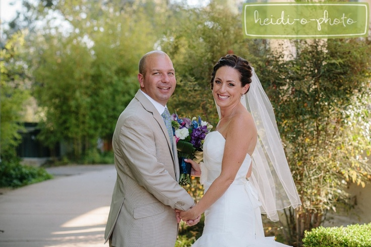 bride & groom - tan suit, veil, purple & blue floral bouquet