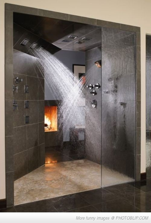 This dual showerhead shower with fireplace and dark stone tile is spacious enough for him and her to enjoy.
