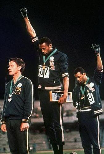 En los Juegos Olímpicos de México de 1968, en la ceremonia de entrega de medallas de la prueba de los 200 metros lisos, Tommie Smith (medalla de oro) junto con su compatriota John Carlos (medalla de bronce) agachó la cabeza y levantó el puño en alto con un guante negro mientras sonaba el himno de los EE.UU. como símbolo del movimiento Black Power y en protesta por el racismo en EE. UU. y el Apartheid en Sudáfrica.