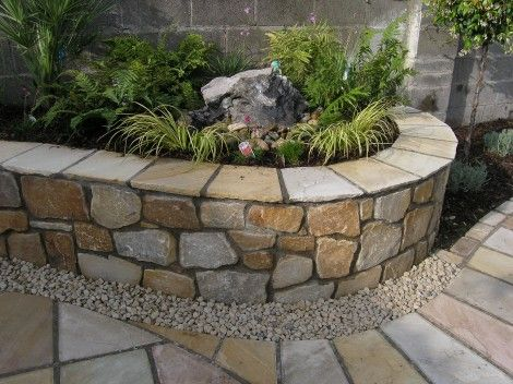 A Raised Bed constructed using random sized natural sandstone and a sandstone wall capping. The results provides an attractive enclosure for a simple garden water feature with a very natural looking collection of ornamental grasses.