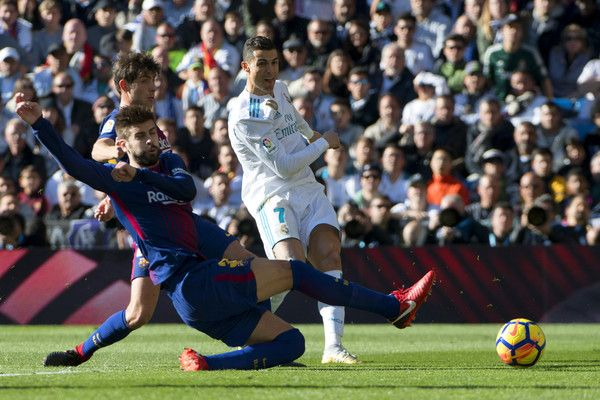 """Barcelona's Spanish defender Gerard Pique (L) vies with Real Madrid's Portuguese forward Cristiano Ronaldo during the Spanish League """"Clasico"""" football match Real Madrid CF vs FC Barcelona at the Santiago Bernabeu stadium in Madrid on December 23, 2017.  / AFP PHOTO / CURTO DE LA TORRE"""