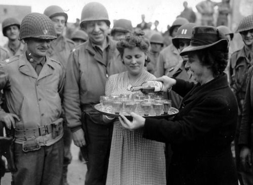 A grateful French women serve drinks to U.S. soldiers following the liberation of Trévières during the Battle of Normandy following the Allied D-Day invasion of France. June 10th, 1944.