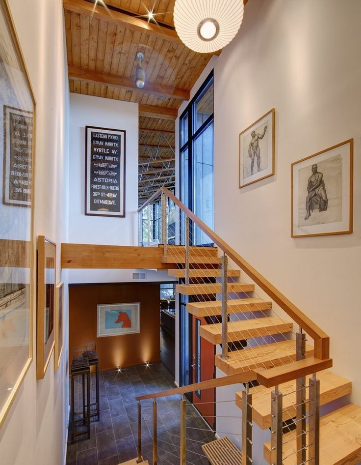 Wooden Floating Staircase With Balustrade Of Horizontal Cable Railing Held In Place By Stainless
