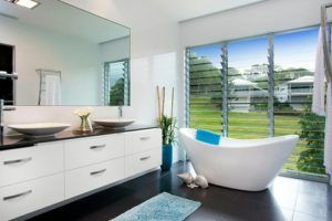 A modern bathroom with freestanding tub, vessel sinks, wide mirrors and flat panel cabinets. / Photo by Presentation Plus