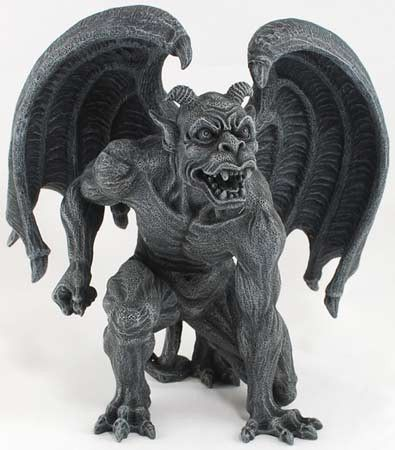 """A fierce gargoyle unfurls his wings, one fist drawn back and every muscle tensed as he prepares to strike. Made out of cold-cast resin, this 6 1/8"""" tall x 6"""" wide statue is a dark charcoal in color, h"""