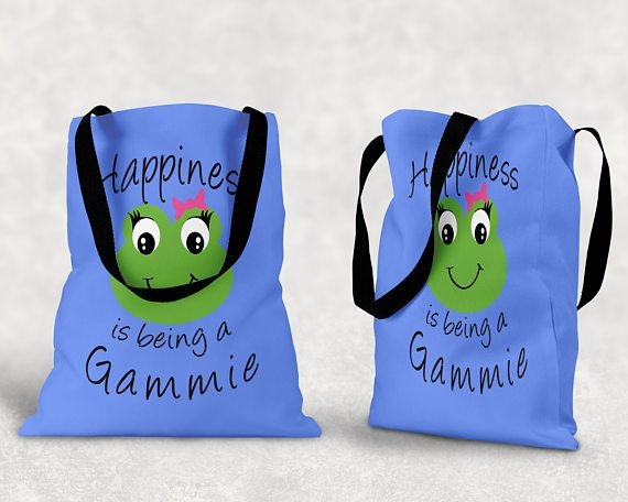 Happiness is being a Gammie  Design printed on front and back 18 x 18 Tote Bag  100% spun polyester poplin fabric  1 inch wide cotton shoulder strap  Black fabric lined  Dry or Spot Clean Only  Four Colors to Choose From - White, Black, Pink or Blue  ***Color may differ slightly from image on screen. Alternate products may appear different hues depending on Fabric. Not all computer monitors and phone resolutions are made equal.