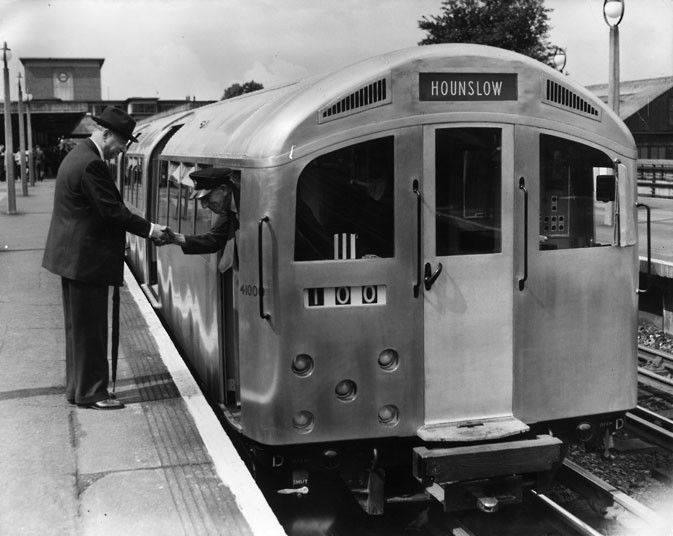 12 August 1957: Sir John Elliott, Chairman of the LTE, shakes hands with the driver of the new prototype 'silver' tube train at Northfields station on the Piccadilly Line