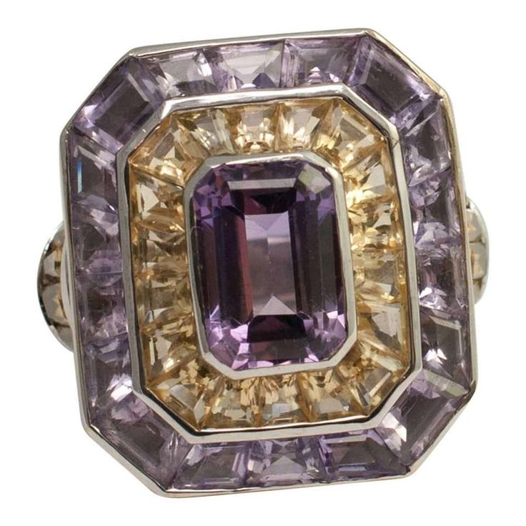 """Theo FENNELL Gold Amethyst Citrine """"Rumba"""" Ring from the iconic English jewellery house; this amazing ring consists of a large step-cut Amethyst surrounded by a row of tapered square-cut Citrines and a further row of tapered square- cut Amethysts all mounted in a rubover setting in 18ct white Gold. At the sides on the shoulders are baguette-cut Citrines forming a curve and joined to a solid banded shank... •$ 7,538.93"""