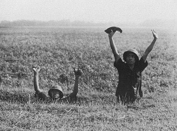 """Indonesische gevangenen (foto H.Wilmar)    Het bijzondere aan de foto, gemaakt ergens op Oost-Java door legerfotograaf Hugo Wilmar, is ook dat het lijkt alsof de afgebeelde Indonesiërs """"Niet schieten!"""" lijken te zeggen tegen de fotograaf. Kijken we echter iets nauwkeuriger dan zien we dat hun blikken naar links gaan, met andere woorden, fotograaf Wilmar stond rechts van een militair die de mannen onder schot hield, zonder dekking. Een gevaarlijk beroep."""