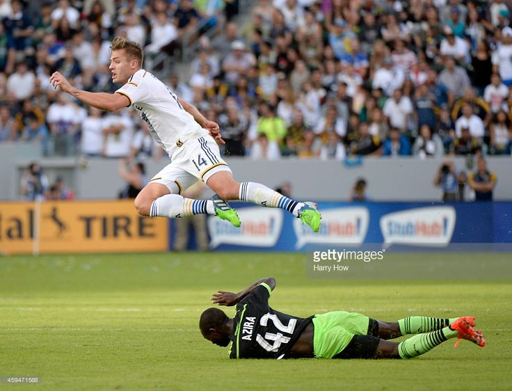 Robbie Rogers #14 of Los Angeles Galaxy is tripped by Micheal Azira #42 of Seattle Sounders FC during the Western Conference Final at StubHub Center on November 23, 2014 in Los Angeles, California.
