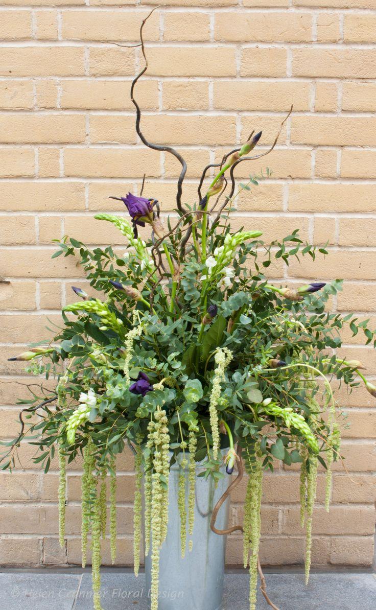 Lush foliage arrangement enhanced with chincherinchee and iris. #wedding