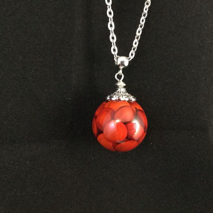 Pendentif bulle de resine et graines rouges sur collier en acier inoxydable.