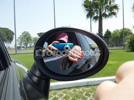 Woman taking selfie in the rearview mirror of the car.