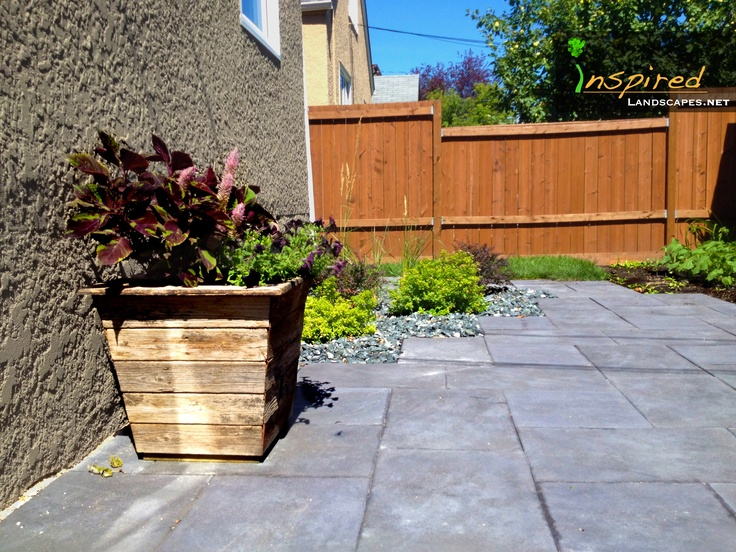 Handmade pot out of recycled cedar made by inspired landscapes. Patio is barkman dynasty slate installed with a inspired touch