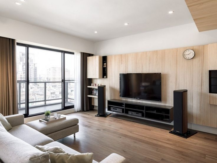 Apartment: Custom Wood Paneling Mixed With Black Floating TV Cabinet Also Comfy L Shaped Sofas Plus Sliding Glass Doors With Brown Curtains: A Modern Apartment Celebrates the Look of Natural Wood