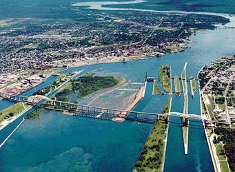 Born & raised and live in Sault Ste. Marie Ontario ( on right side of the photo) which is directly across from Sault Ste. Marie, Michigan ( to the left)  Photo showing the Soo Locks where lake freighters cross from Lake Huron into Lake Superior or vice versa