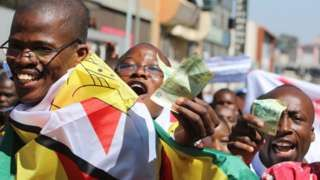 Protesters holding old Zimbabwe dollar notes in Harare, Zimbabwe - Wednesday 3 August 2016