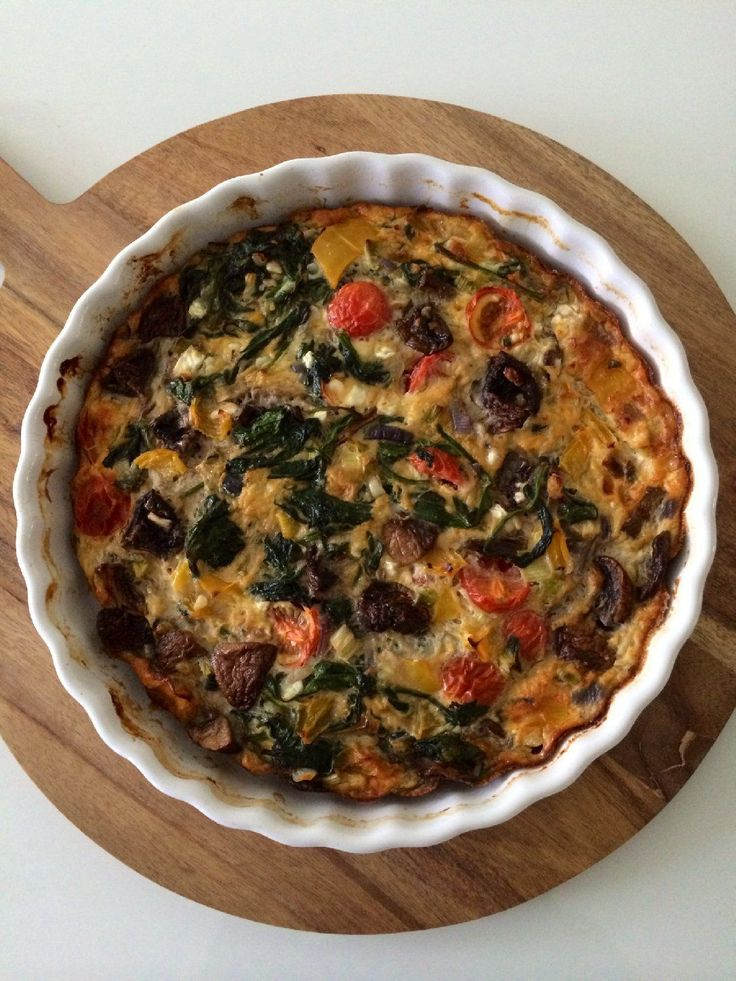 Kha - Hüttenkäse quiche (2 personen)  Wat heb je nodig: – quichevorm of ovenschaal – olijfolie – 1 teentje knoflook – 1 rode ui – bosje lenteui – 1 gele paprika – 200 gr. kastanjechampignons – 200 gr. gewassen spinazie – handjevol tomaatjes – 5 eieren – 250 gr. hüttenkäse – snufje zout en versgemalen peper