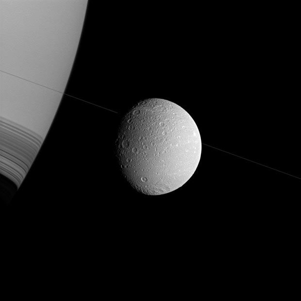 Saturn and its moon Dione appear in this image which was taken in visible green light at approximately 35,000 miles (57,000 kilometres) from Dione.