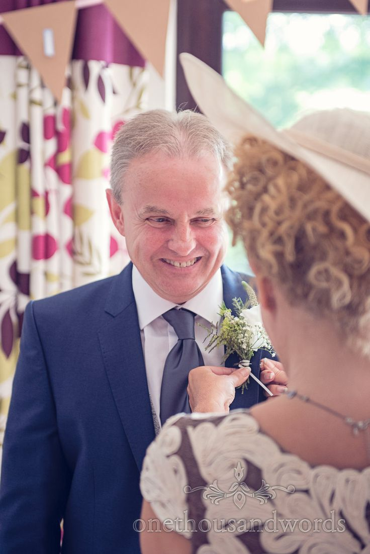 Father of the bride in blue wedding suit has button hole added on wedding morning. Photography by one thousand words wedding photographers
