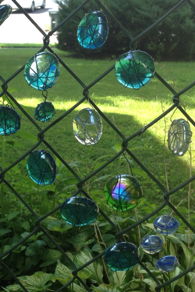 Glass water gems I wrapped with wire and put up in my chain link fence.
