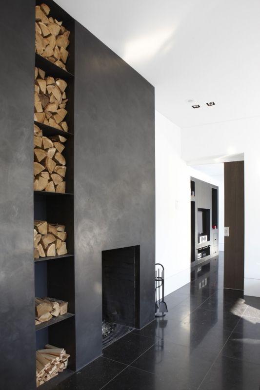 Design inbouwhaard in donkere wand met schappen voor houtopslag - interieur Piet Boon
