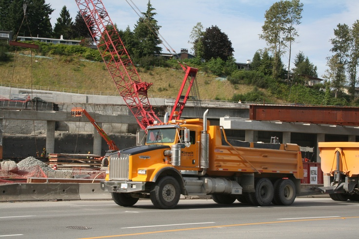 A Kiewit-Flatiron dump truck passes in front of the Manitowoc heavy-lifting crane.