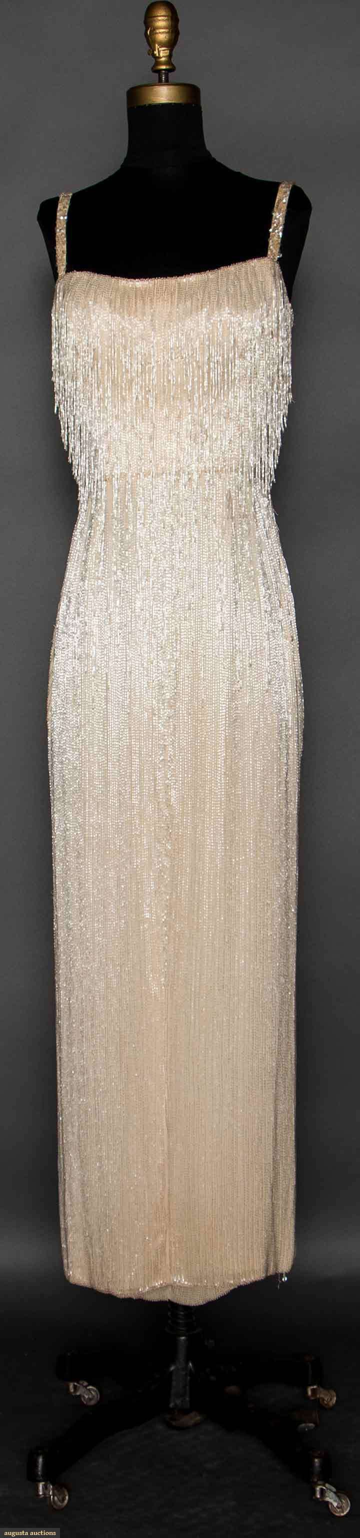 HATTIE CARNEGIE BEAD ENCRUSTED GOWN, LATE 1950s White silk sheath completely covered in rows of small, white bugle beads, neckline to hip w/ rows of beaded fringe, irridescent sequin straps, CF kick pleat, labeled