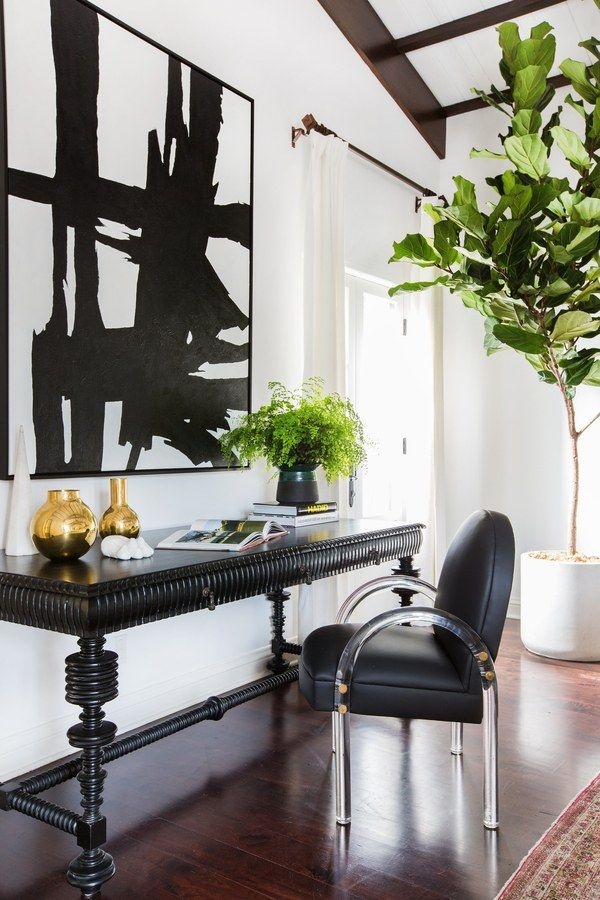 Elegant vignette with a black table, a modern black chair, and large art
