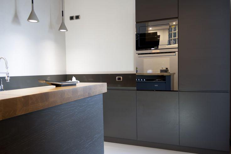 Il legno di frassino con poro aperto, incontra l'eleganza degli elettrodomestici in cristallo nero, con penisola Snek in lamellare al naturale, un connubio perfetto per una cucina raffinata